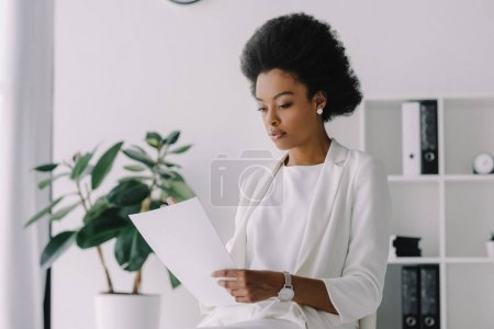 attractive african american businesswoman reading document in office