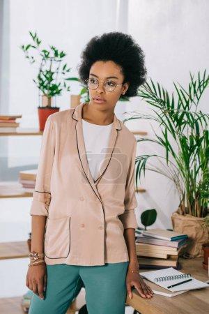 Photo pour Attrayante femme afro-américaine debout près de la table au bureau et à la recherche de suite - image libre de droit
