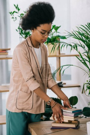 attractive african american businesswoman putting books on table in office