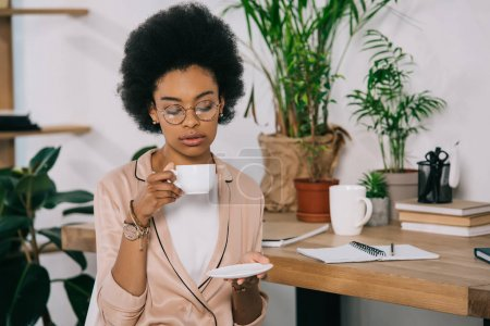 Photo for Attractive african american businesswoman drinking coffee in office during coffee break - Royalty Free Image