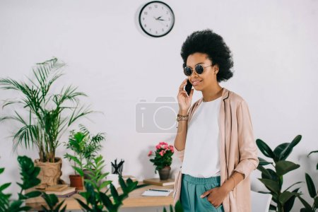 smiling attractive african american businesswoman talking by smartphone in office