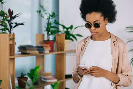 attractive african american businesswoman in sunglasses using smartphone in office