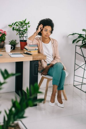 Photo for Attractive african american businesswoman sitting on chair and looking away in office - Royalty Free Image