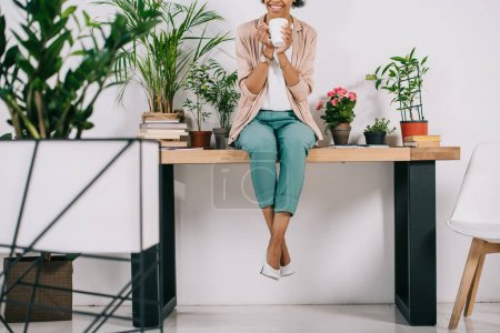 Photo for Cropped image of african american businesswoman sitting on table with cup of coffee in office - Royalty Free Image