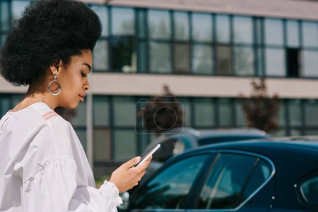 side view of attractive african american businesswoman using smartphone on parking