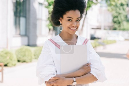 attractive smiling african american businesswoman standing on street with laptop