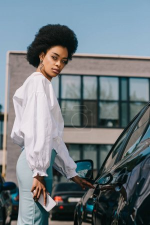attractive african american businesswoman opening car on parking