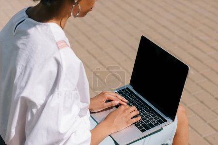 Foto de Imagen recortada de empresaria afroamericana sentada en Banco y utilizando la computadora portátil en la calle - Imagen libre de derechos