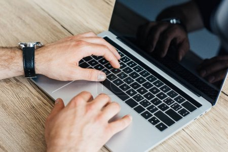 close-up partial view of person typing on laptop with blank screen