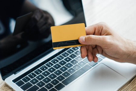 close-up partial view of person holding credit card near laptop