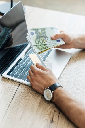 partial view of person holding credit card and euro banknotes at workplace with laptop