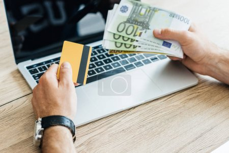 cropped shot of person holding credit card and euro banknotes above laptop
