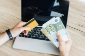 cropped shot of person holding credit card and money above laptop