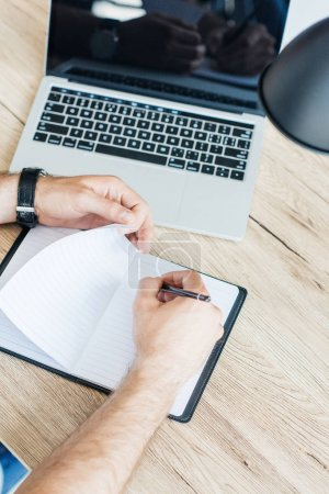 high angle view of person writing in blank notebook at workplace