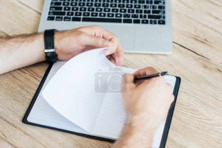 partial view of person writing in notebook at wooden table