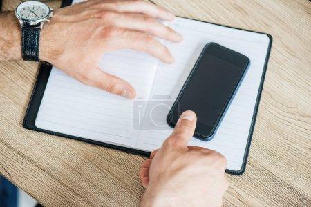 recortar el tiro de manos masculinas con smartphone con pantalla en blanco