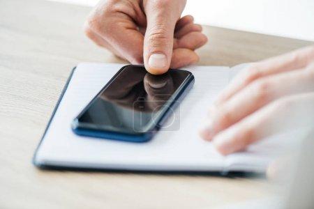 gros plan vue partielle de la personne à l'aide de smartphone avec écran blanc, mise au point sélective