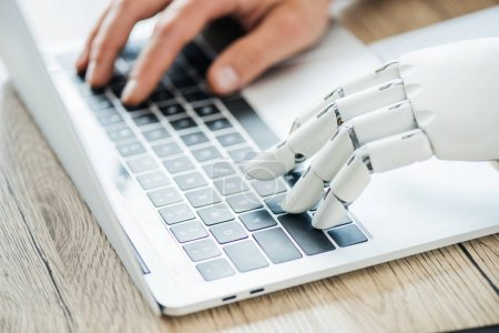 Photo for Close-up view of human and robot hands typing on laptop at workplace - Royalty Free Image