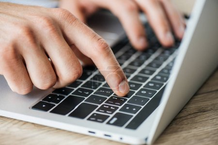 close-up partial view of person typing on laptop, selective focus