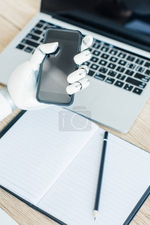 close-up view of hand of robot holding smartphone with blank screen at workplace