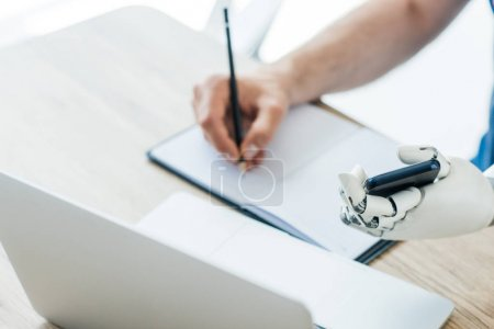 Photo for Selective focus of robotic arm holding smartphone and human hand taking notes at workplace - Royalty Free Image