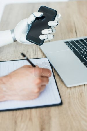 close-up view of robotic arm holding smartphone and human hand taking notes at wooden table