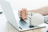 close-up view of human and robot fists on laptop at wooden table