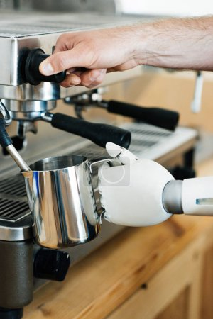 close-up view of robotic arm and human hand using coffee machine