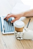 robotic arm holding disposable coffee cup and human hand using laptop at wooden table