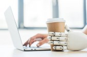 close-up view of robotic arm holding disposable coffee cup and human hand using laptop