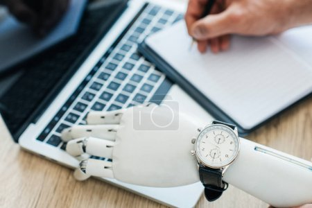 selective focus of robotic arm with wristwatch using laptop and human hand taking notes at wooden table