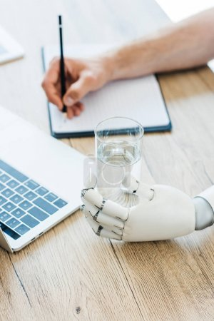 Photo for Close-up view of robotic arm holding glass of water and person taking notes at wooden table - Royalty Free Image