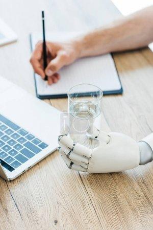 Photo pour Vue rapprochée du bras robotisé tenant du verre d'eau et de la personne prenant des notes à une table en bois - image libre de droit
