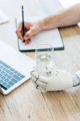 close-up view of robotic arm holding glass of water and person taking notes at wooden table