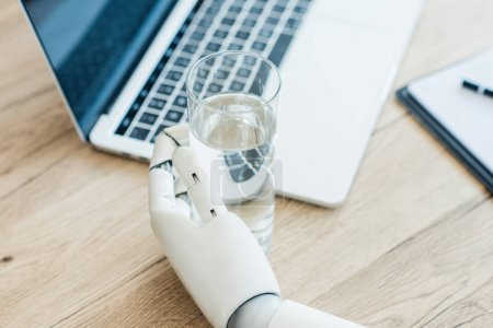 close-up view of hand of robot holding glass of water at wooden table
