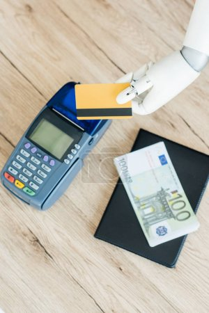 top view of hand of robot holding credit card above payment terminal and money on wooden table