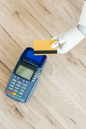 top view of hand of robot holding credit card above payment terminal on wooden table