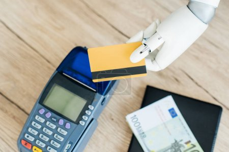 close-up view of hand of robot holding credit card above money and payment terminal on wooden table