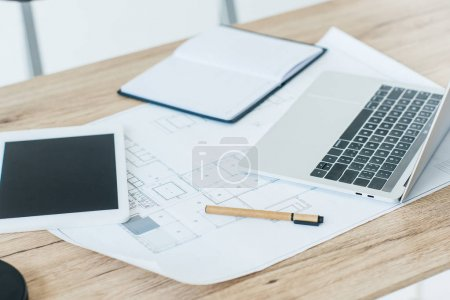 close-up view of digital tablet, blueprint, laptop and notebook on table
