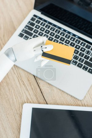 close-up view of robot holding credit card above laptop and digital tablet