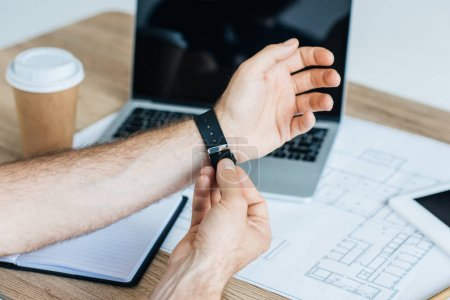 cropped shot of person wearing smartwatch at workplace