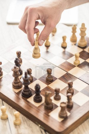 close-up partial view of person playing chess at wooden table