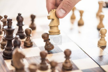 cropped shot of human hand playing chess, selective focus