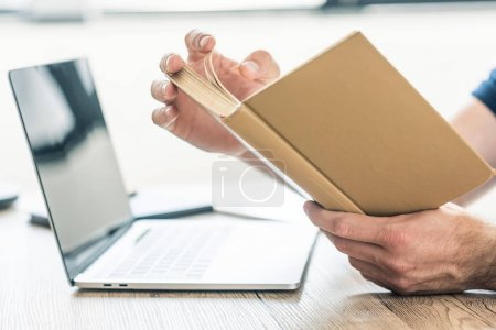 close-up partial view of person holding book at table with laptop