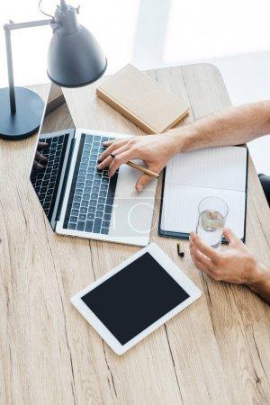 recorta la foto de la persona sosteniendo el vaso de agua y el uso de laptop en el lugar de trabajo