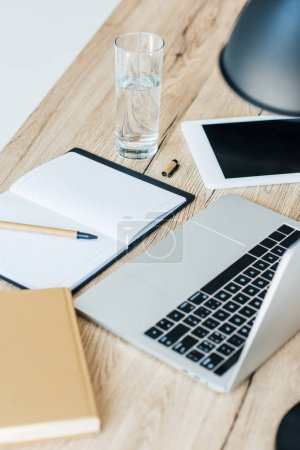 close-up view of laptop, digital tablet, glass of water and notebook at workplace