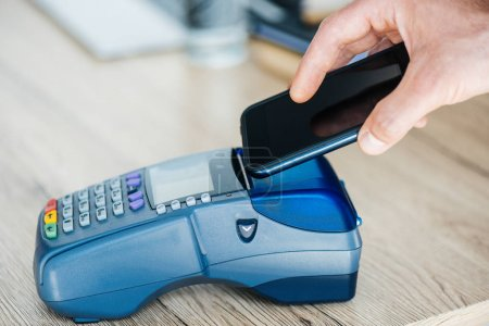 Photo for Cropped shot of person using smartphone and payment terminal - Royalty Free Image