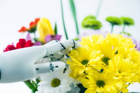 close-up view of hand of robot and beautiful flowers on white