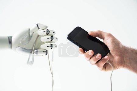 Photo pour Vue rapprochée du robot tenant des écouteurs et la main de l'homme tenant smartphone isolé sur blanc - image libre de droit