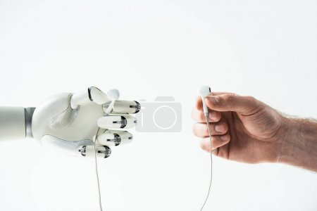 Photo for Close-up view of robotic arm and human hand holding earphones isolated on white - Royalty Free Image